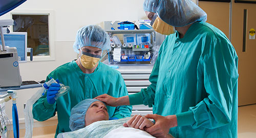 Two nurses intubating a patient for surgery