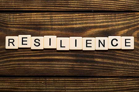 Resilience Spelled Out in Scrabble Letters on a Dark Wooden Table