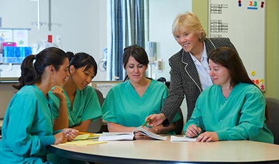 Nurses reviewing a book with a nurse educator